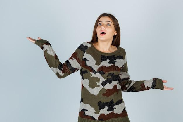 Jonge dame in trui die handpalmen opzij spreidt en perplex kijkt
