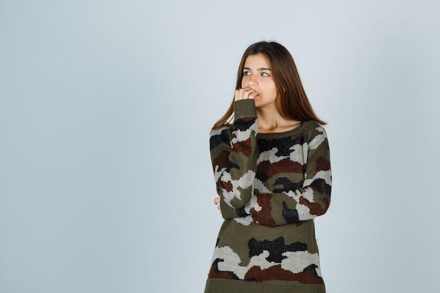 Jonge dame in trui haar nagels bijten en peinzend kijken