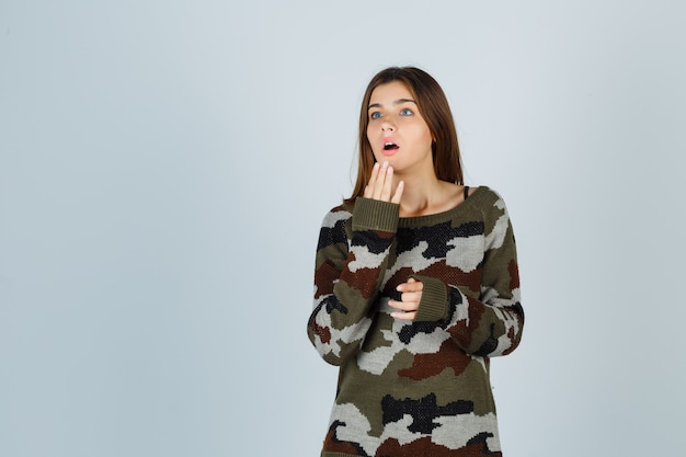 Jonge dame in trui hand in hand in de buurt van mond en verbaasd op zoek