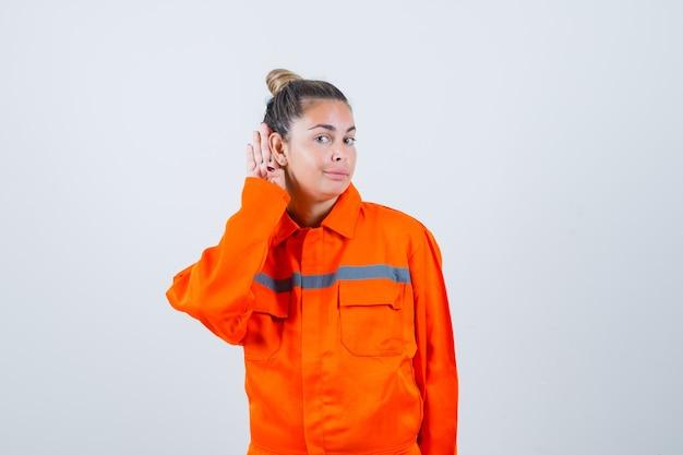 Jonge dame in uniform werknemer luisteren en kijken aandachtig, vooraanzicht.