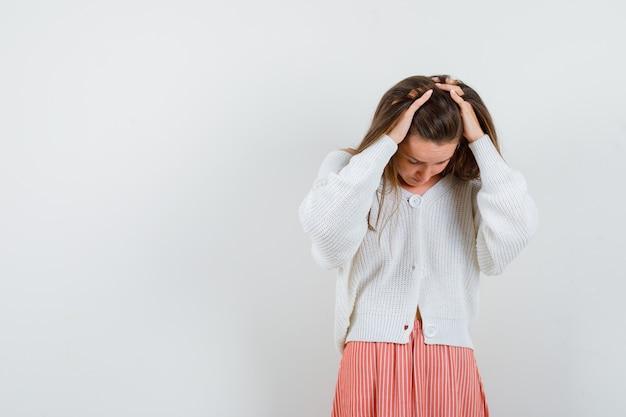 Jonge dame in vest en rok hand in hand op het hoofd op zoek vergeetachtig geïsoleerd