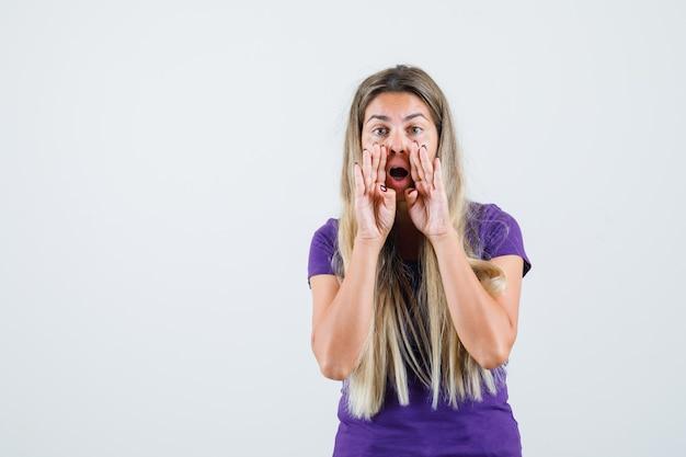 Jonge dame in violet t-shirt geheim vertellen met handen dichtbij mond, vooraanzicht.