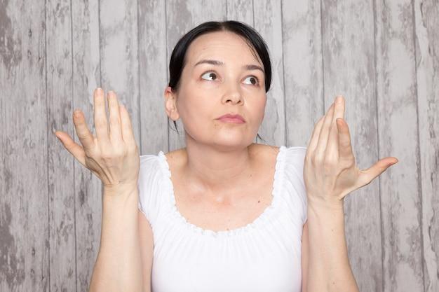 Jonge dame in wit overhemd emoties handen aan de orde gesteld op grijze muur