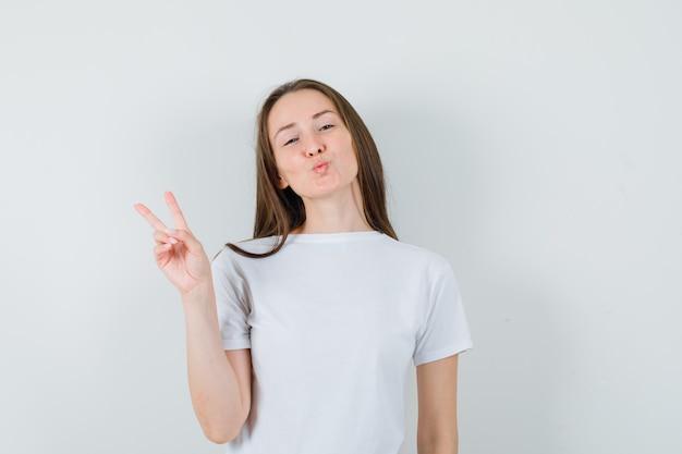 Jonge dame in wit t-shirt die het pruilende lippen van het overwinningsgebaar toont en er zelfverzekerd uitziet