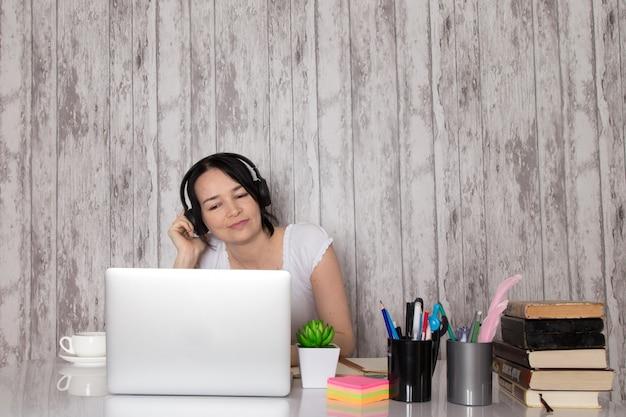 Jonge dame in wit t-shirt zwarte koptelefoon met behulp van grijze laptop op tafel kopje koffie plant pennen boeken over grijs