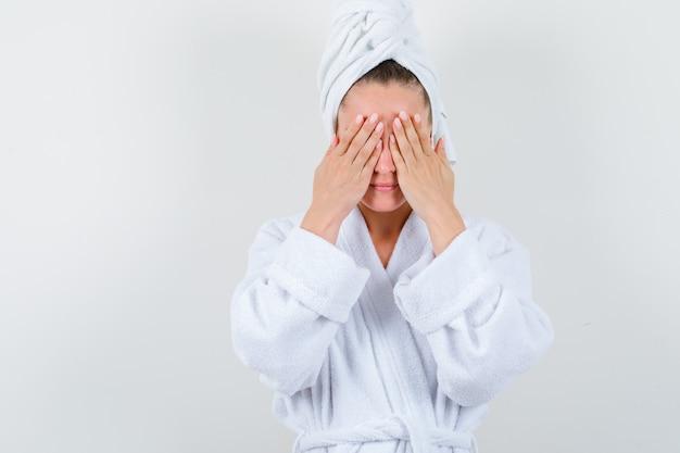 Jonge dame in witte badjas, handdoek die ogen met handen bedekt en wrokkig kijkt, vooraanzicht.