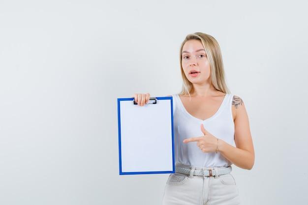 Jonge dame in witte blouse die naar leeg klembord richt en aandachtig kijkt