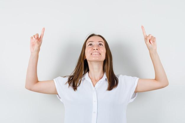 Jonge dame in witte blouse die omhoog wijst terwijl glimlachend en gelukkig kijkt