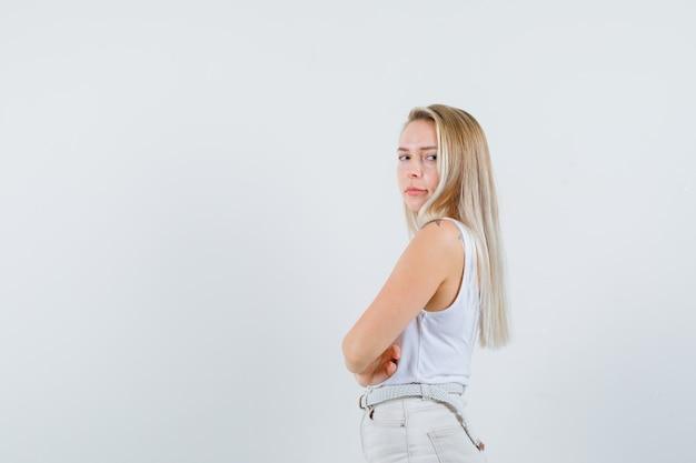 Jonge dame in witte blouse die opzij kijkt en ernstig kijkt. ruimte voor tekst