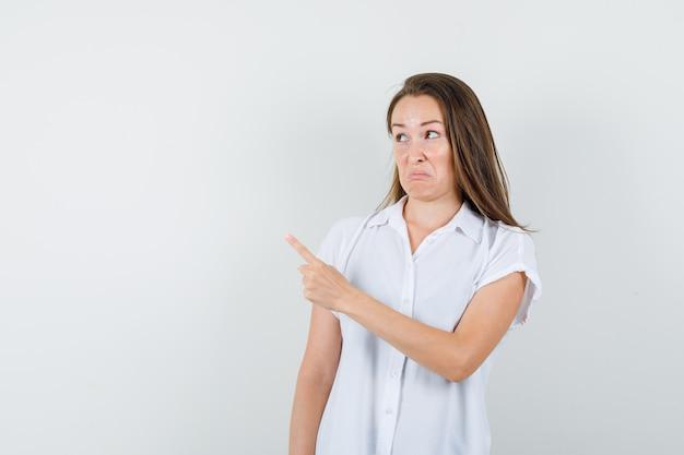 Jonge dame in witte blouse die opzij wijst en geïrriteerd kijkt