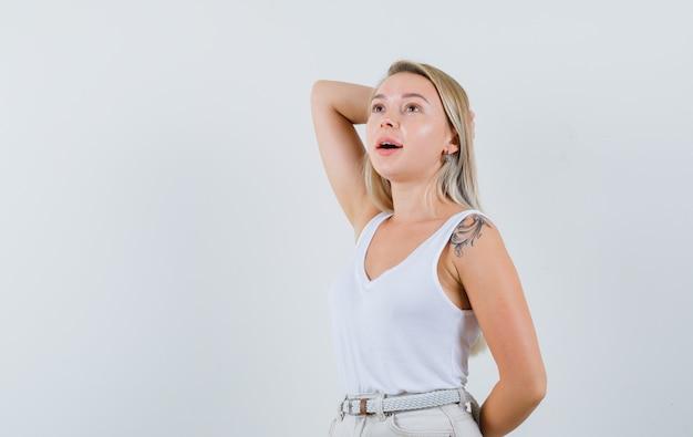 Jonge dame in witte blouse poseren met de hand achter het hoofd en ziet er indrukwekkend uit