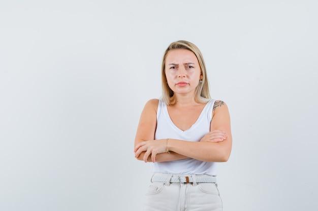 Jonge dame in witte blouse staan terwijl de armen gekruist en beledigd kijken