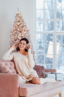 Jonge dame in witte jurk op de bank in de kersttijd