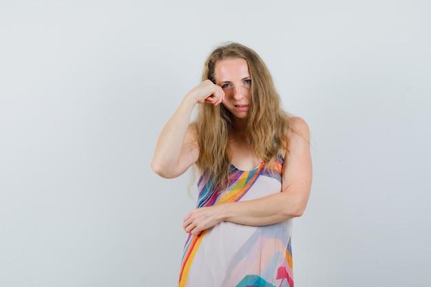 Jonge dame in zomerjurk trekt haar huid op de wang