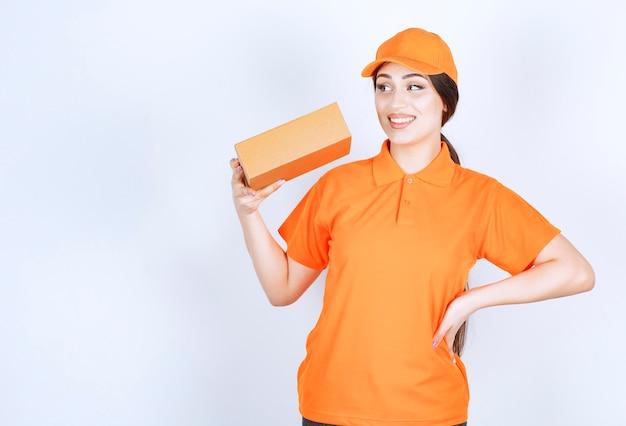 Jonge dame is klaar om te bezorgen, oranje unshape en pakket