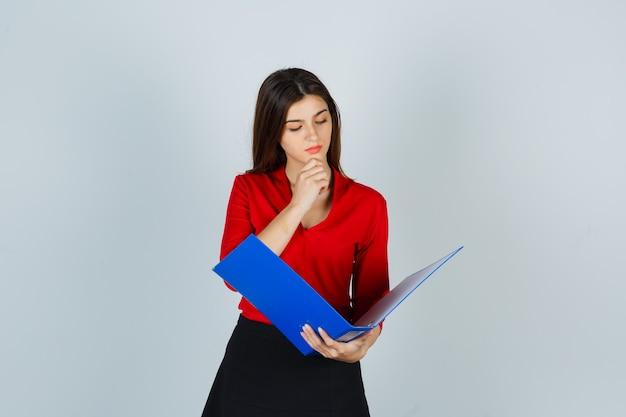 Jonge dame kijkt door map in rode blouse, rok en kijkt gericht