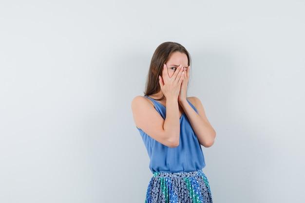 Jonge dame kijkt door vingers in blouse, rok en kijkt opgewonden, vooraanzicht.