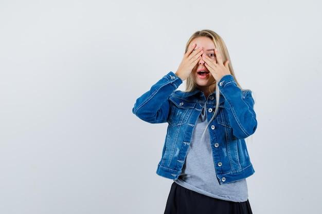 Jonge dame kijkt door vingers met oog in t-shirt, spijkerjasje, rok en ziet er schattig uit