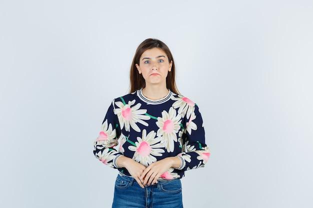 Jonge dame kijkt naar camera in blouse, spijkerbroek en kijkt teleurgesteld. vooraanzicht.