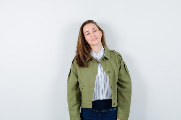 Jonge dame kijkt naar de camera in shirt, jas en ziet er charmant uit. vooraanzicht.