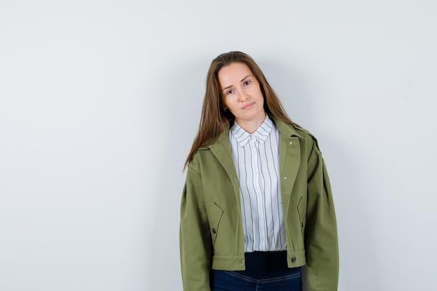Jonge dame kijkt naar de camera in shirt, jas en ziet er schattig uit. vooraanzicht.