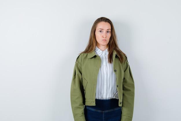 Jonge dame kijkt naar de camera in shirt, jas en ziet er verstandig uit. vooraanzicht.