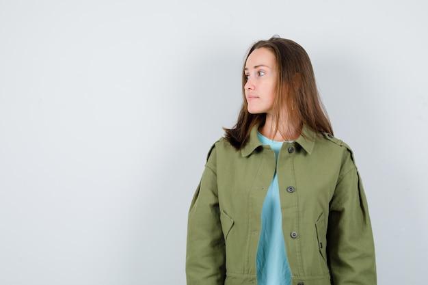 Jonge dame kijkt weg in t-shirt, jas en kijkt peinzend, vooraanzicht.
