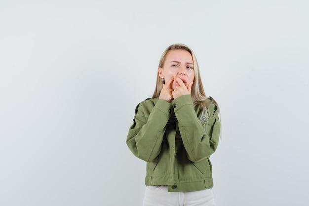 Jonge dame knijpen haar puistje op de wang in jas, broek, vooraanzicht.