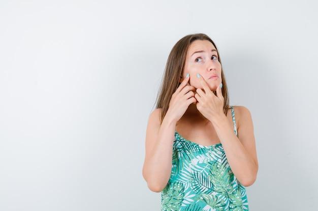 Jonge dame knijpt haar puistje op de wang in blouse en kijkt peinzend, vooraanzicht.