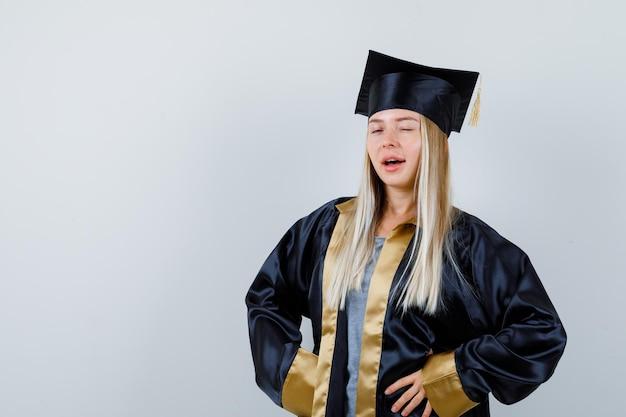 Jonge dame knippert naar de camera in academische jurk en ziet er zelfverzekerd uit.