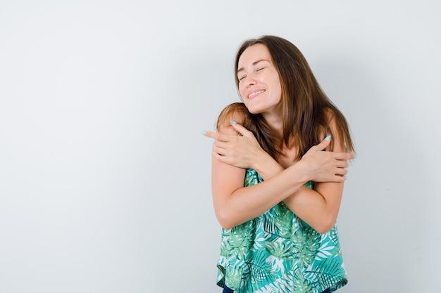 Jonge dame knuffelt zichzelf in blouse en ziet er mooi uit, vooraanzicht.