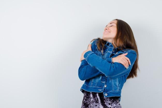 Jonge dame knuffelt zichzelf in blouse, spijkerjasje en ziet er ontspannen uit, vooraanzicht.
