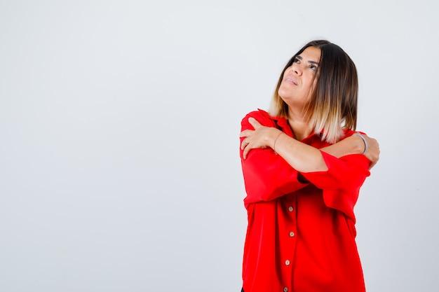 Jonge dame knuffelt zichzelf in een rood oversized shirt en ziet er vredig uit, vooraanzicht.
