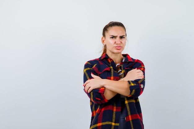Jonge dame knuffelt zichzelf in top, geruit hemd en ziet er teleurgesteld uit. vooraanzicht.