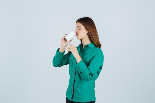 Jonge dame koffie drinken uit plastic beker in shirt en op zoek gericht. vooraanzicht.