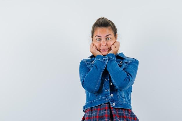 Jonge dame kussen gezicht op haar handen in shirt, jasje en op zoek schattig, vooraanzicht.