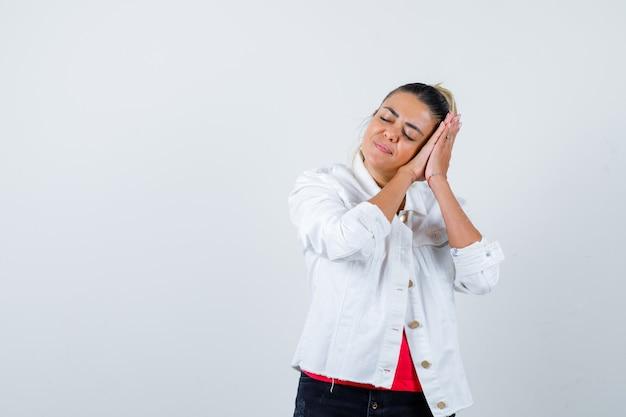 Jonge dame leunend op handen als kussen in t-shirt, witte jas en ziet er vredig uit, vooraanzicht.