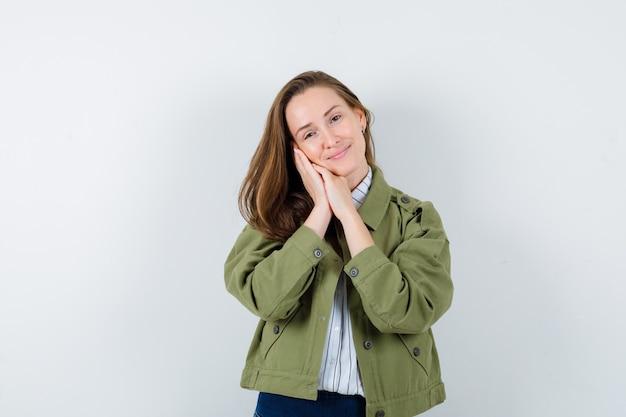 Jonge dame leunend op handpalmen als kussen in shirt, jas en ziet er schattig uit, vooraanzicht.