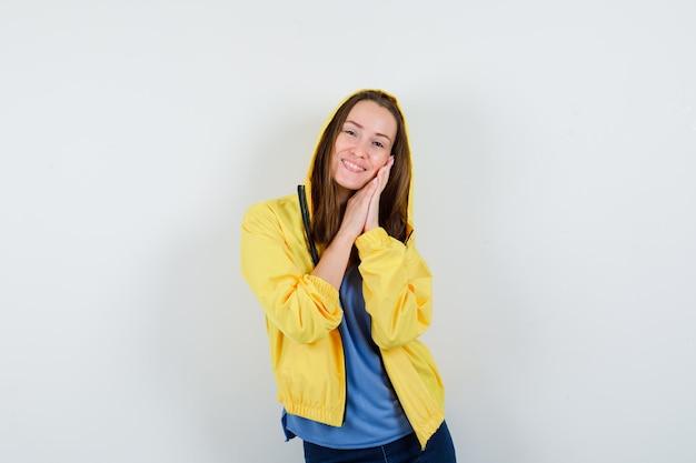 Jonge dame leunend op handpalmen als kussen in t-shirt, jas en ziet er schattig uit