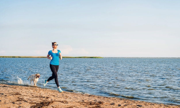 Jonge dame loopt. vrouwenagent die bij het zonnige strand van het de zomerzand lopen. training in de buurt van de oceaan zee kust. mooi fit meisje. fitness model kaukasische etniciteit buitenshuis. gewichtsverlies oefening. joggen.