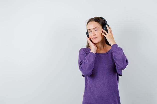 Jonge dame, luisteren naar muziek met koptelefoon in violet overhemd en op zoek heerlijk, vooraanzicht.
