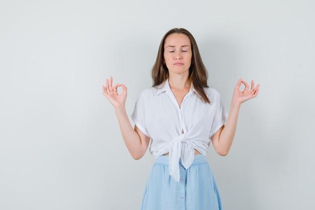 Jonge dame mediteren in blouse, rok en kalm op zoek