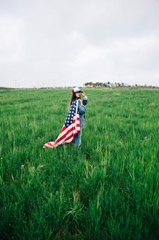 Jonge dame met amerikaanse vlag camera kijken