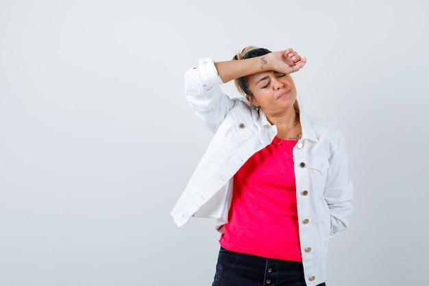 Jonge dame met arm op voorhoofd in t-shirt, witte jas en ziet er moe uit, vooraanzicht.