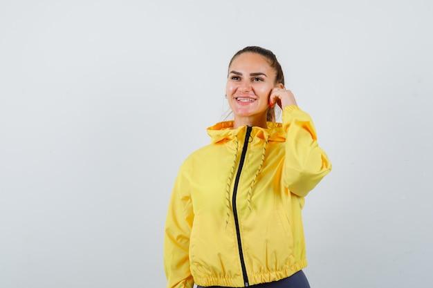 Jonge dame met de hand op de wang terwijl ze lacht in een gele jas en er vrolijk uitziet. vooraanzicht.