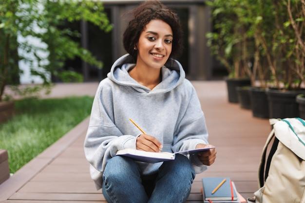 Jonge dame met donker krullend haar zitten en het maken van aantekeningen in notitieboekje terwijl gelukkig