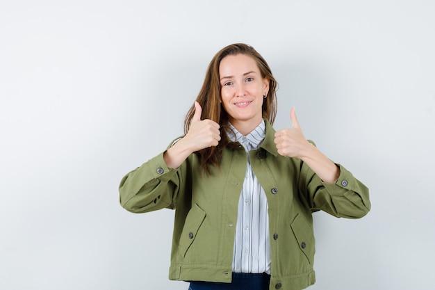 Jonge dame met dubbele duimen in shirt, jas en zelfverzekerd. vooraanzicht.