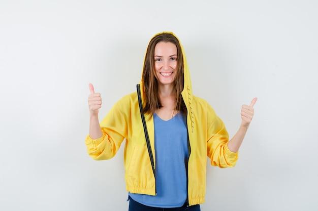 Jonge dame met dubbele duimen omhoog in t-shirt, jas en zelfverzekerd. vooraanzicht.