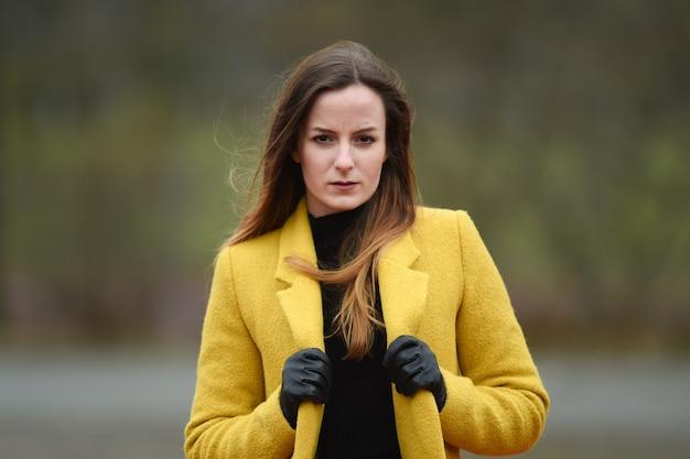 Jonge dame met gele jas mode portretfoto's