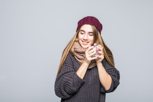 Jonge dame met griep en koude dranken warme drank kruiden tee om gezond te worden op grijs